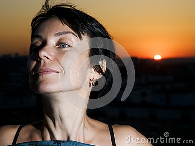 Woman and sunset in a city