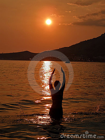 Woman at sunset in sea 1