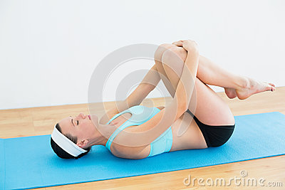 Woman in supine wind release posture on yoga mat