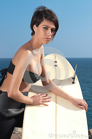 Woman with surfboard under blue sky