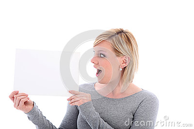 Woman with surprised expression holding sign