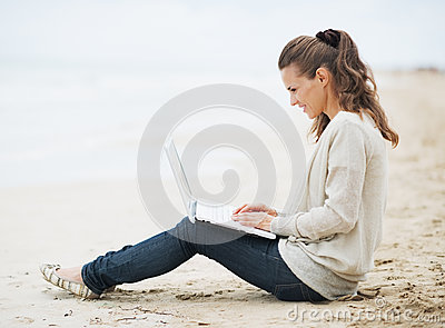 Woman in sweater sitting on beach and using laptop
