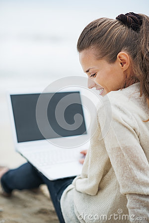 Woman in sweater sitting on lonely beach and using laptop