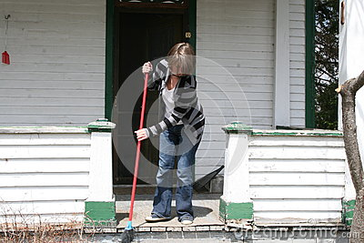 Woman sweeping front porch