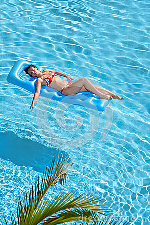 Woman in swimsuit bakes on inflatable mattress