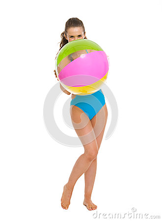 Woman in swimsuit hiding behind beach ball