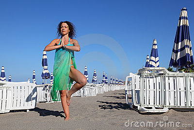 Woman in swimsuit and pareo stands on beach