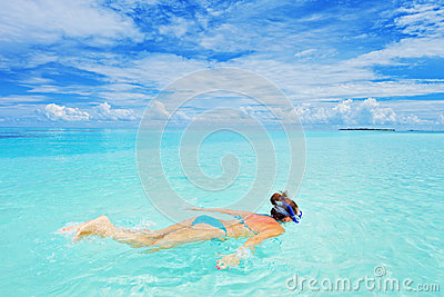 A woman in swimsuit snorkeling at Maldives island