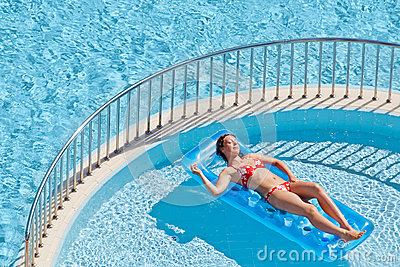 Woman in swimsuit sunbathes lying on inflatable mattress