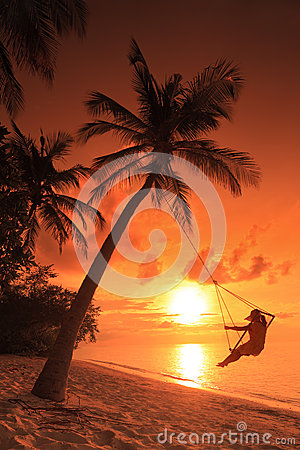 Woman swinging on a sunset