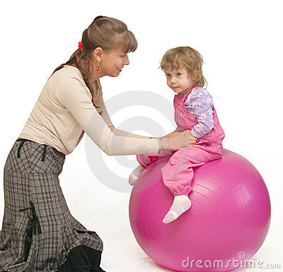 The woman swings the child on fitball