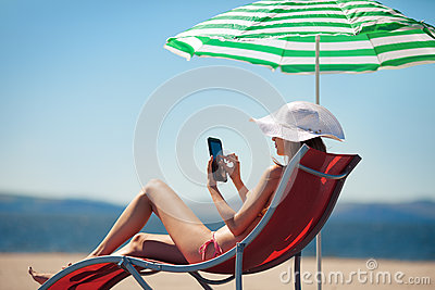 Woman with tablet computer in deck chair
