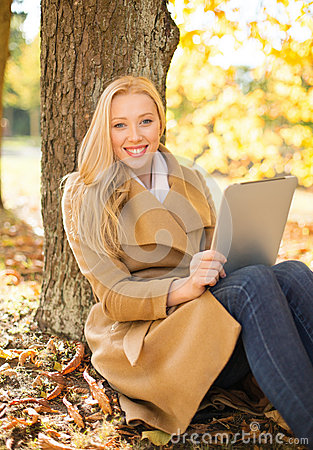 Woman with tablet pc in autumn park