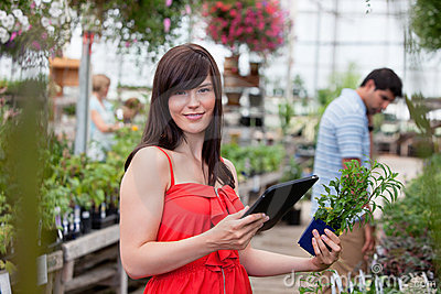Woman with tablet pc and potted plant