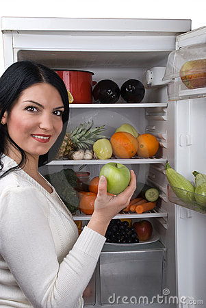 Woman take green apple from fridge