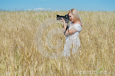 Woman take a photo with camera in a field