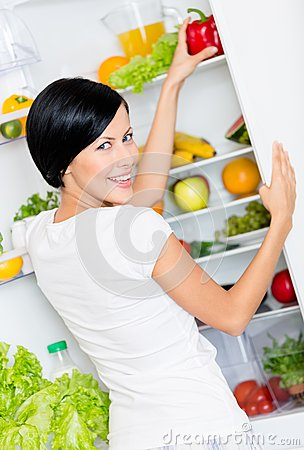 Woman takes bell pepper from opened refrigerator