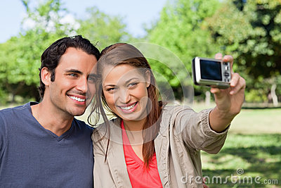 Woman takes a picture of her friend and herself with a camera
