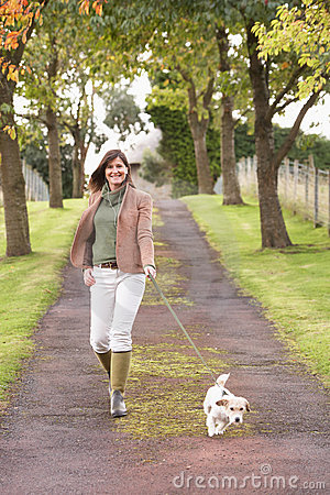 Woman Taking Dog For Walk Outdoors In Autumn Park