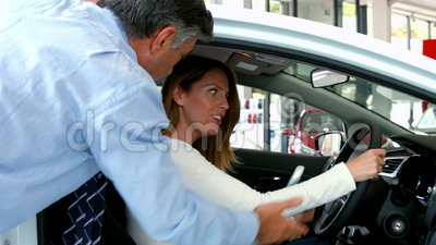 Woman taking a look at a new car. At the car showroom stock video