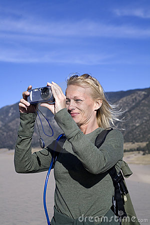 Woman taking nature photo in sand