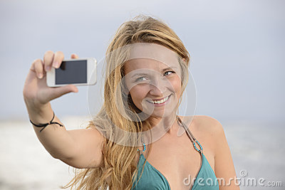 Woman taking photo with cellphone on the beach
