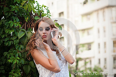 Woman talking on mobile phone, looking down. Outdo