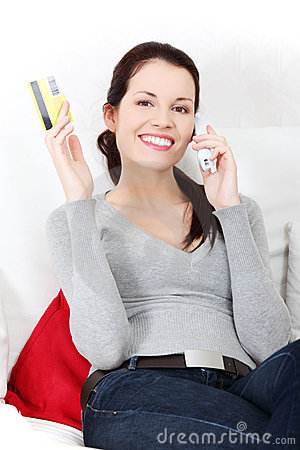 Woman talking on the phone, holding a credit card.