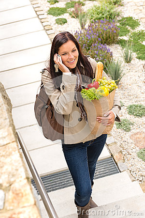Woman talking smart phone walking speaking bag