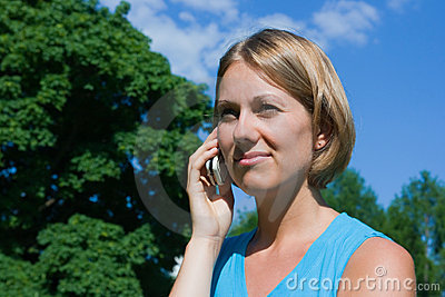 The woman talks by a mobile phone