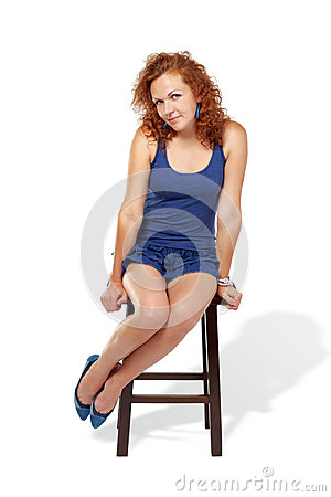 Woman in tank top dress sits on stool