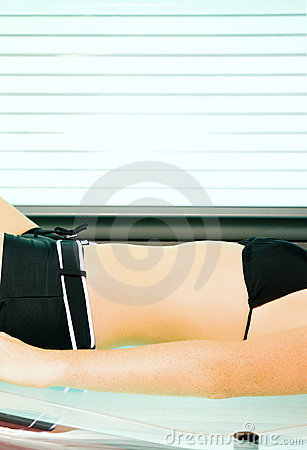 Woman tanning in solarium