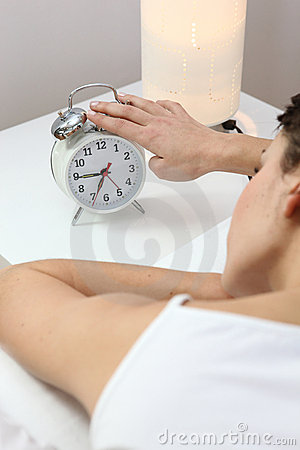 Woman tapping an alarm clock