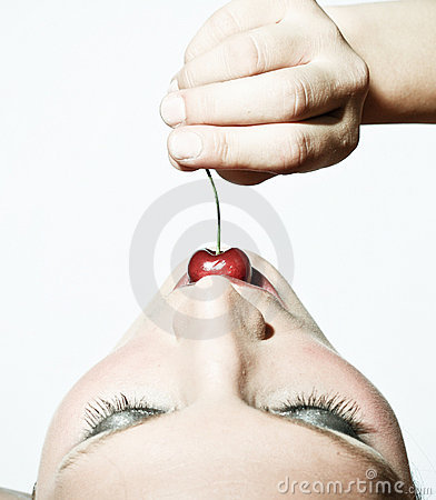 Woman Tasting A Cherry In Contrast