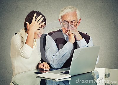 Woman teaching confused elderly man how to use laptop Stock Photo