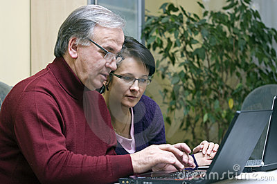 Woman teaching Senior use of computers
