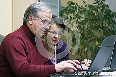Woman teaching Senior use of computers