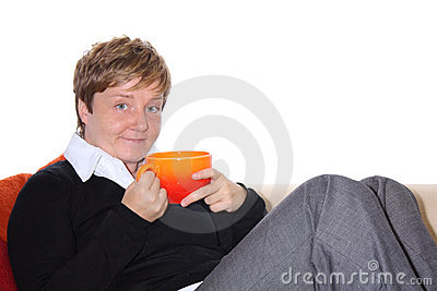 Woman with Teacup is relaxing on a Sofa