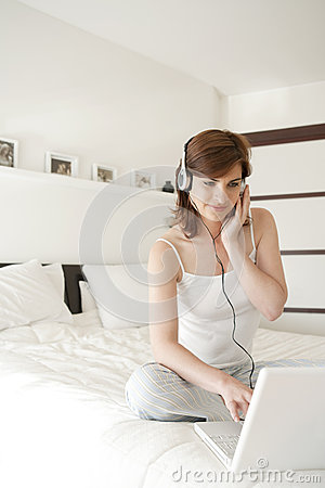 Woman With Technology In Bedroom