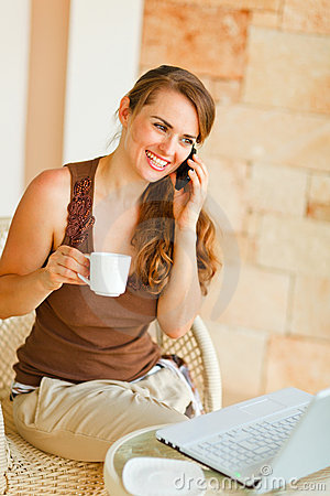 Woman on terrace with laptop speaking mobile