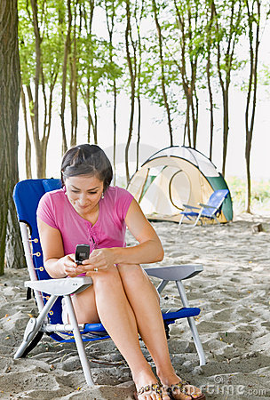 Woman text messaging on cell phone at campsite