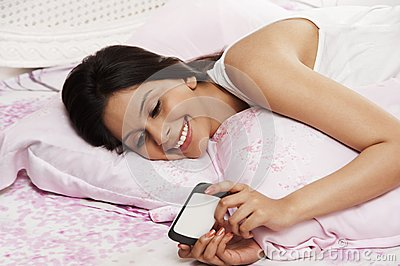 Woman text messaging on a mobile phone on the bed