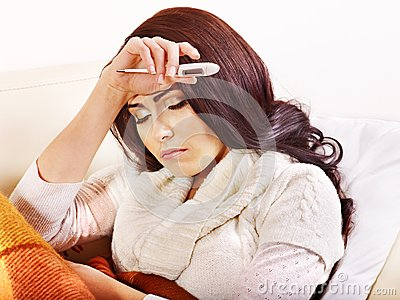 Woman with thermometer having  flue in bed.
