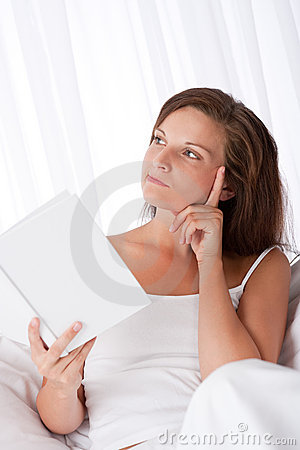Woman thinking while reading book
