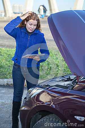 Woman in thought standing near car with tablet pc