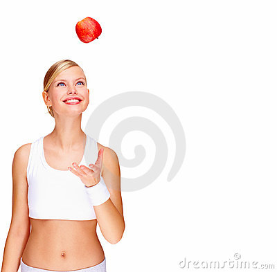 Woman tossing an apple over white background