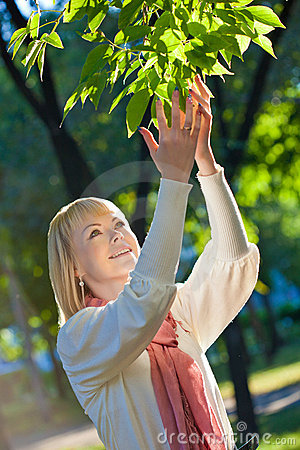 Woman touching tree leaves