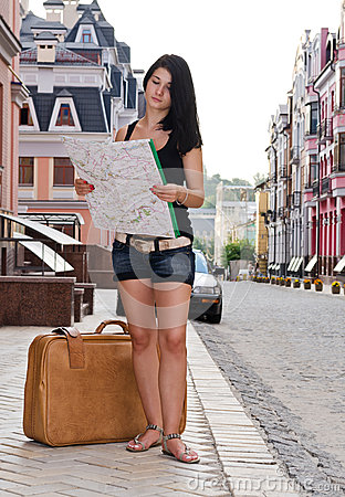Woman tourist with luggage and map
