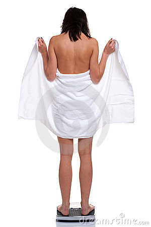 Woman in towel weighing herself