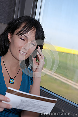 Woman in a train talking on the phone smiling
